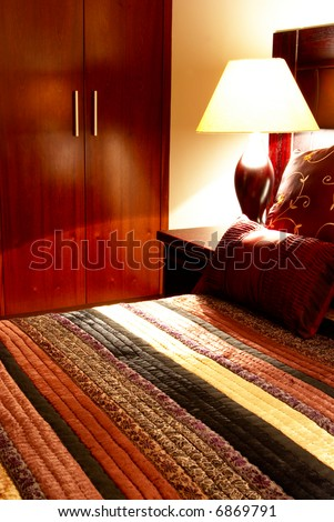 Colorful cushions on a bed in a guest lodge with the cupboard in the back - stock photo