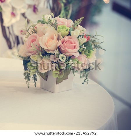 Colorful decoration artificial flower in jar on table (vintage), process color - stock photo