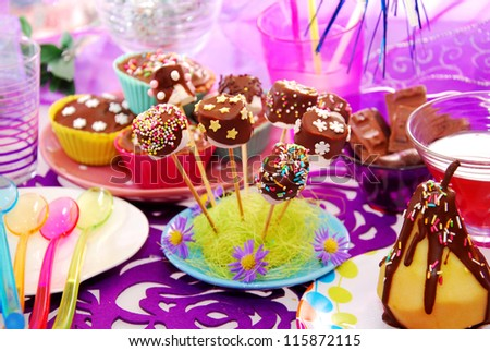 colorful decoration of birthday party table with cake and sweets for child
