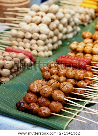 colorful delicious grilled meat ball on banana leaves in a street food night market in THAILAND, tourist attraction THAI food lifestyle on streets in big towns such as BANGKOK PHUKET and CHIANGMAI - stock photo
