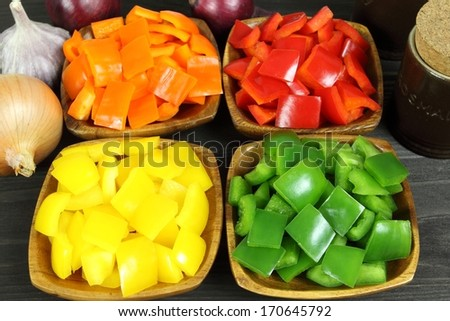 Colorful diced peppers in a wooden bowls - stock photo