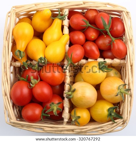Colorful different kind tomatoes in wooden basket. - stock photo