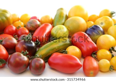 Colorful different kind tomatoes on white background. - stock photo