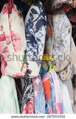 Colorful display of assorted trendy scarves with floral patterns hanging on rails in a shop or street market, close up view