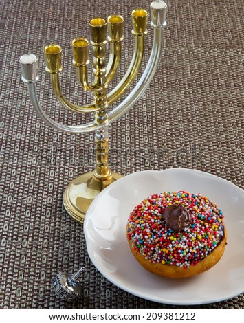 Colorful donut, silver dreidel and menorah  for Hanukkah celebration. - stock photo