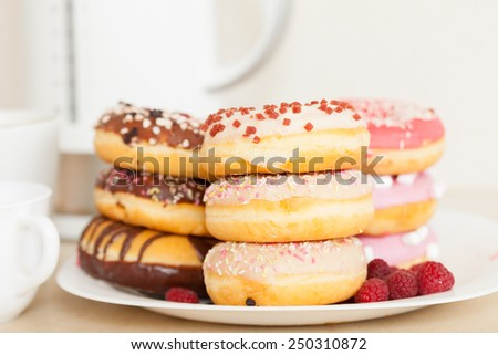 colorful donuts on  white plate on  kitchen table. - stock photo
