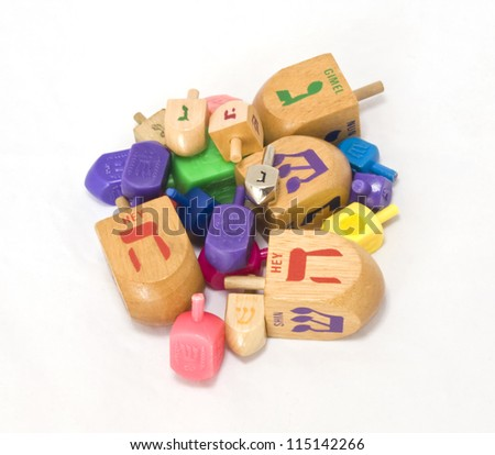Colorful dreidles for Chanukah isolated on a white background. Players spin the dreidle and win or lose depending on which Hebrew letter appears on the top of the fallen dreidle. - stock photo