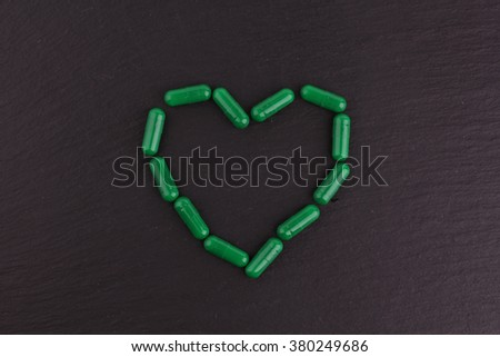 Colorful drug pills in shape of heart on dark background, pharmaceutical concept