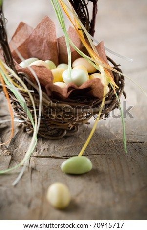 Colorful easter candy in brown basket with ribbon - stock photo