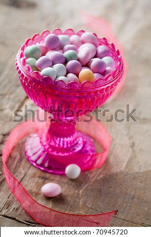 Colorful easter candy in pink glass bowl - stock photo