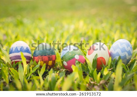 colorful Easter egg in the fresh spring meadow. - stock photo