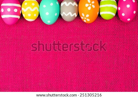 Colorful Easter egg top border over a pink burlap background - stock photo