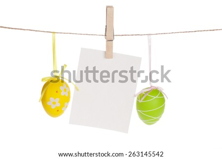 Colorful easter eggs and blank photo frame hanging on rope. Isolated on white background - stock photo
