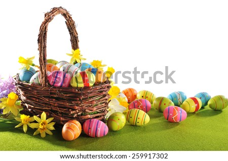 colorful easter eggs and narcissus in easter nest on grass - stock photo