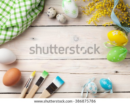 Colorful easter eggs and paint brushes on wooden table. Top view with copy space - stock photo