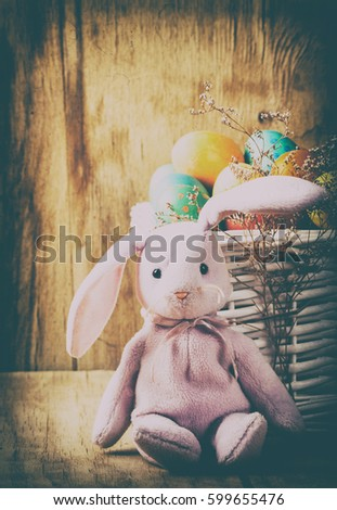 Colorful easter eggs and rabbit close up on wood desk