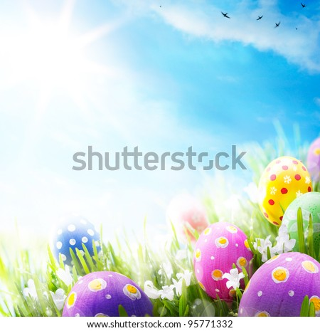 Colorful Easter eggs decorated with flowers in the grass on blue sky background - stock photo