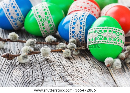 Colorful Easter eggs decorated with lace and willow branch on wooden background. Selective focus, copy space - stock photo