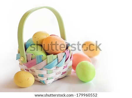 Colorful Easter eggs in a basket on white background - stock photo