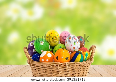 Colorful Easter eggs in a basket on wood texture on green flower background.