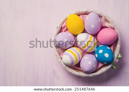 Colorful Easter eggs in a basket, with space for text. Top view - stock photo