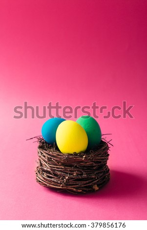 Colorful Easter eggs in bird nest on pink background - stock photo