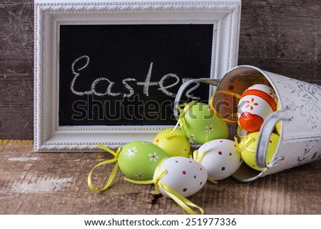 Colorful easter eggs in bucket and board with word Easter on wooden background. Easter background. - stock photo