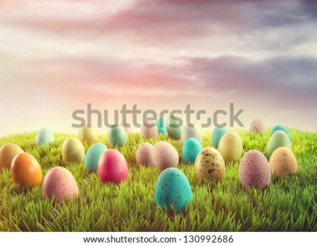 Colorful Easter eggs in grass at sunrise