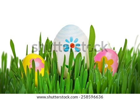 Colorful Easter eggs in grass isolated on white - stock photo
