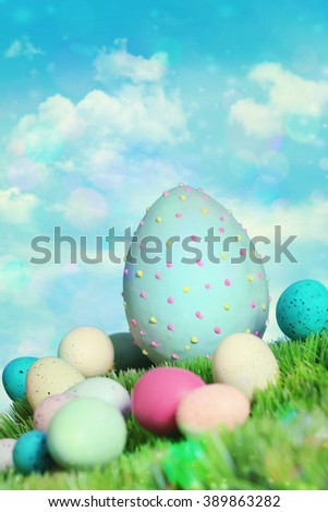 Colorful easter eggs in grass with blue sky - stock photo