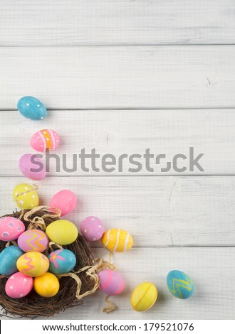 Colorful Easter Eggs in Nest from Top Side View on White or Gray Rustic Wood Background with room or space for copy, text, words  - stock photo