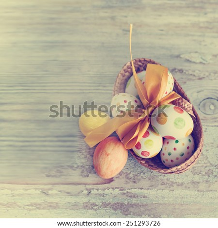 Colorful easter eggs in the basket with yellow bow. Background with easter eggs. With retro filter effect - stock photo