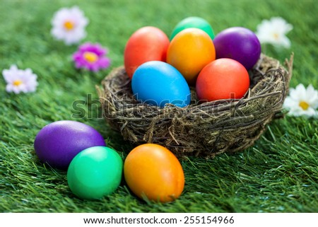 colorful Easter eggs in the nest on the green grass - stock photo