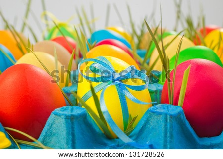 Colorful easter eggs in tray with grass - stock photo