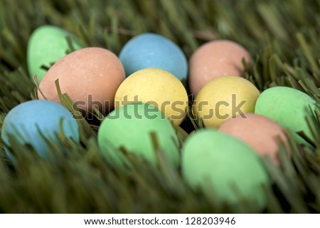Colorful Easter eggs laid on green grass - stock photo
