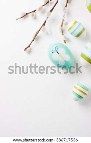 Colorful Easter eggs on a bright background with willow branches and copy space, top view - stock photo