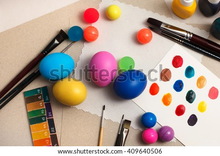 Colorful easter eggs on the table with brushes