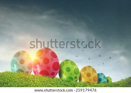 Colorful Easter eggs painted with dots on a grass field - stock photo
