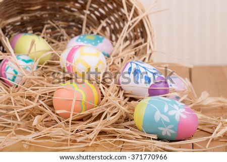 Colorful Easter eggs spilled from a basket - stock photo