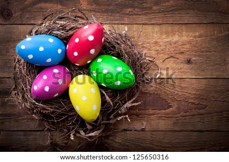 Colorful easter eggs with white points in straw nest on a wooden table - stock photo