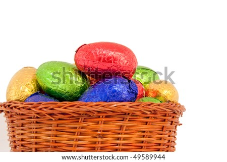 colorful easter eggs wrapped in shiny foil in wicker basket isolated white background