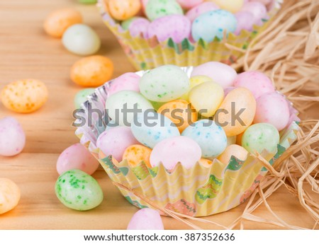 Colorful Easter jelly beans in paper cups on a wood background
