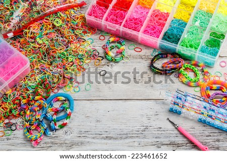 Colorful elastic loom bands with band loom, bracelets, tools and hobby box - stock photo