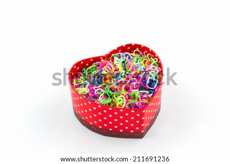 Colorful elastic rainbow loom bands in gift box shaped heart on white background.