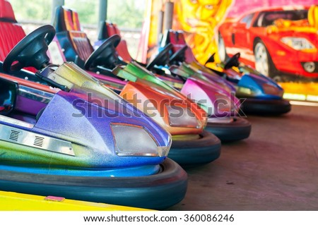 Colorful electric bumper car in autodrom in the fairground attractions at amusement park. Selective focus on the cars - stock photo