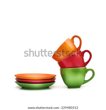 Colorful empty mugs stacked over white background