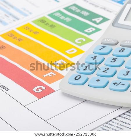 Colorful energy efficiency chart with calculator - studio shot - stock photo