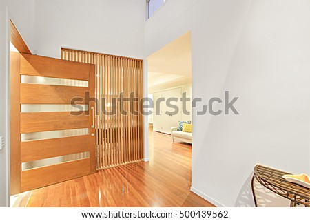 Colorful Entrance And Wooden Door With Designs, Walls Are Painted With  White Color, Floor
