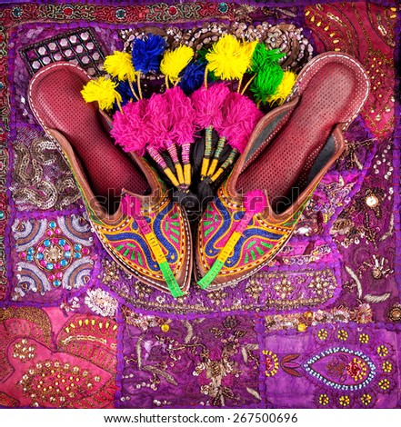 Colorful ethnic shoes and camel decorations on violet Rajasthan cushion cover on flea market in India - stock photo
