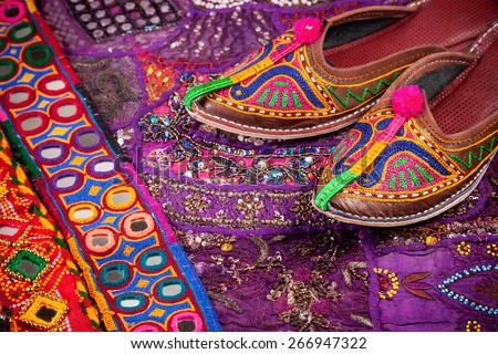 Colorful ethnic shoes, cushion cover and Rajasthan belts on flea market in India - stock photo